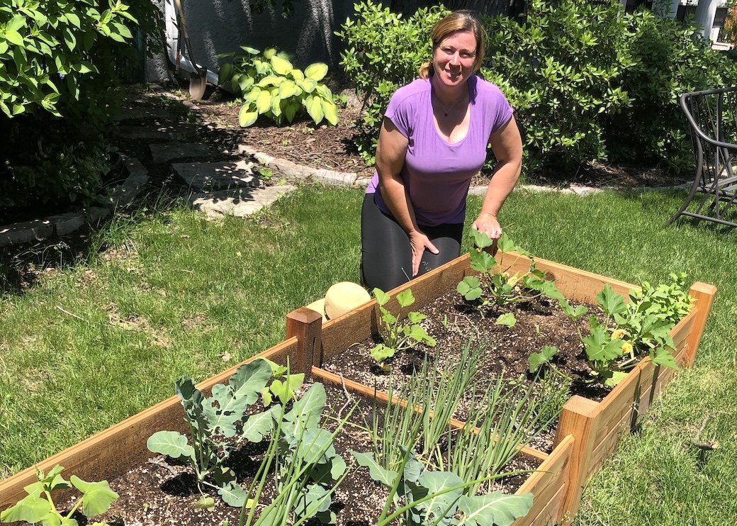 Image of woman by her raised bed vegetable garden
