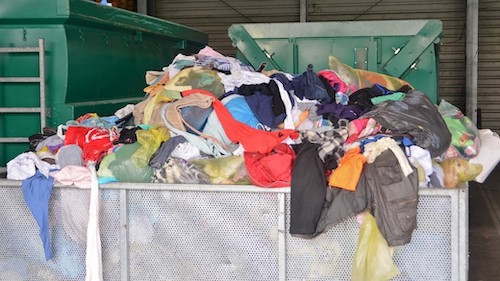 Photo of dumpster full of clothing