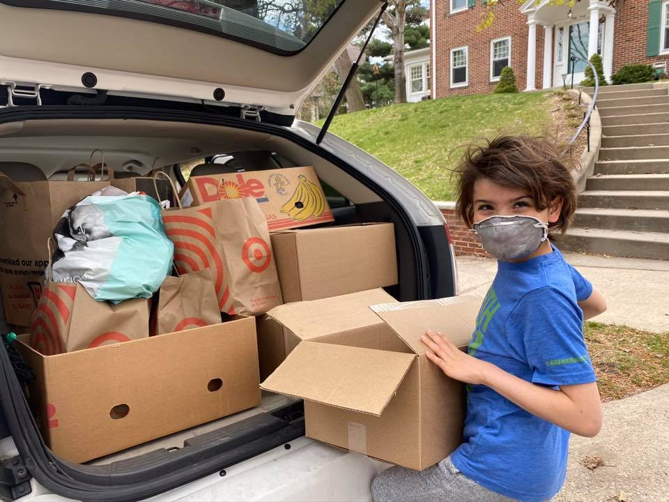 Image of child loading donations into car