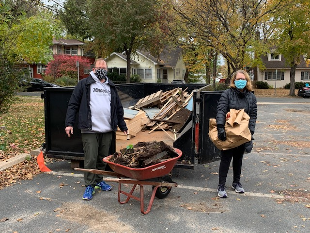image of two people by dumpster with load in wheelbarrow